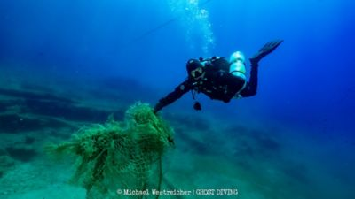 A diver from Ghost Divers recovering a lost fishing net underwater.