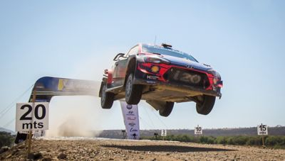 The Hyundai i20 Coupe WRC in mid-air during a rally.