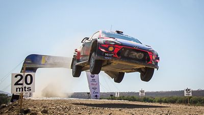 Hyundai i20 Coupe WRC lifting off the ground whilst being driven on a gravel road