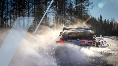 The Hyundai i20 Coupe WRC car creating some spray in the snow.