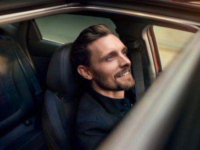 Spokojeně vzhlížející muž ve svém voze Hyundai