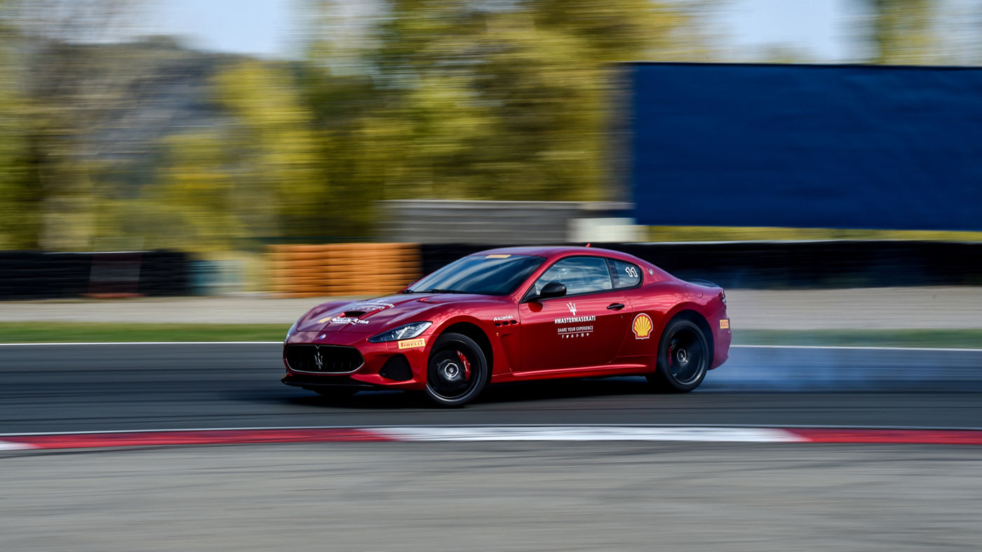 Maserati GranTurismo with partners' logos running on a circuit