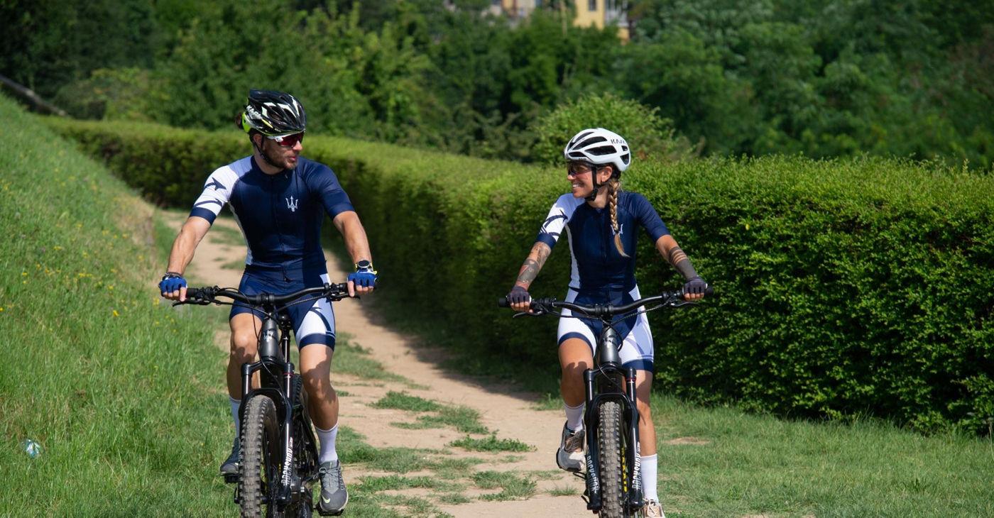 Ein Mann und eine Frau beim Fahrradfahren mit Maserati Fahrradtrikot