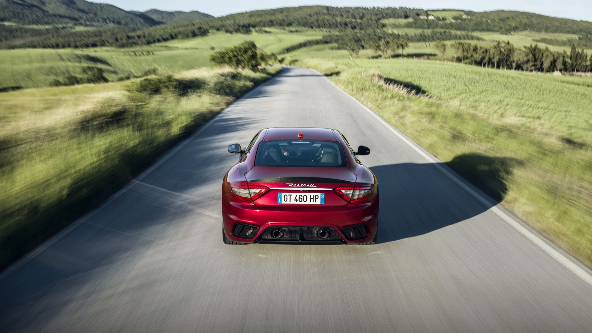 On the road: rear view of a red Maserati GranTurismo