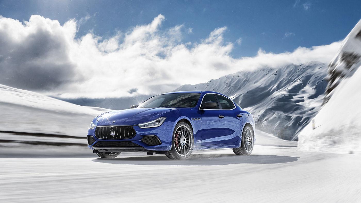A blue Maserati Ghibli running on a snowy road