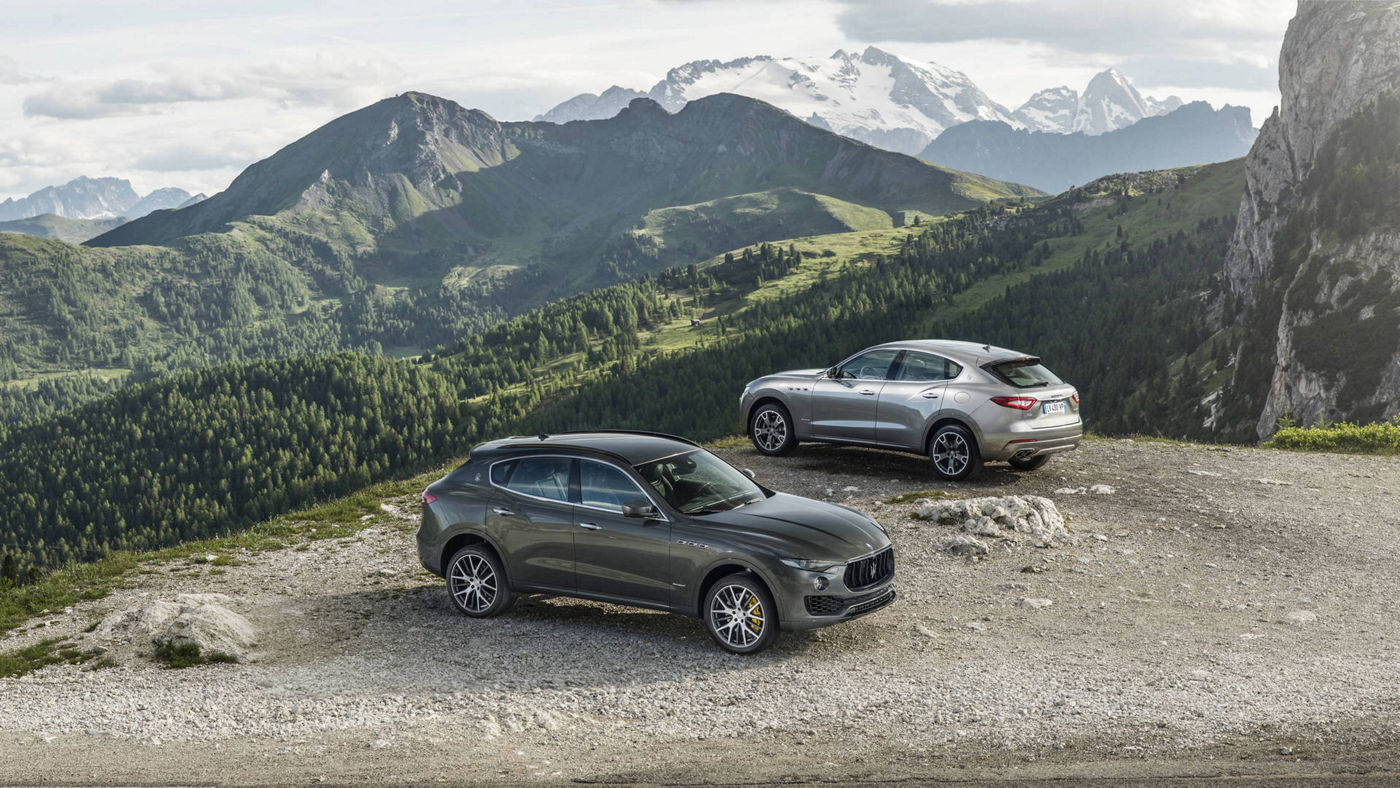A Grey and a dark grey Maserati Levante models on the road.