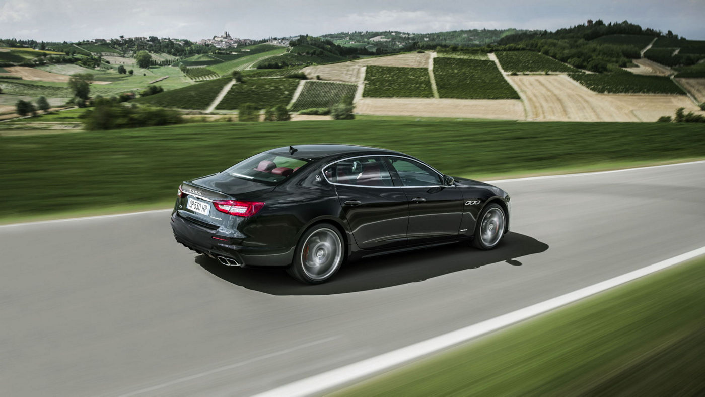 Black Maserati Quattroporte GranLusso - Driving on the road, rear and side view