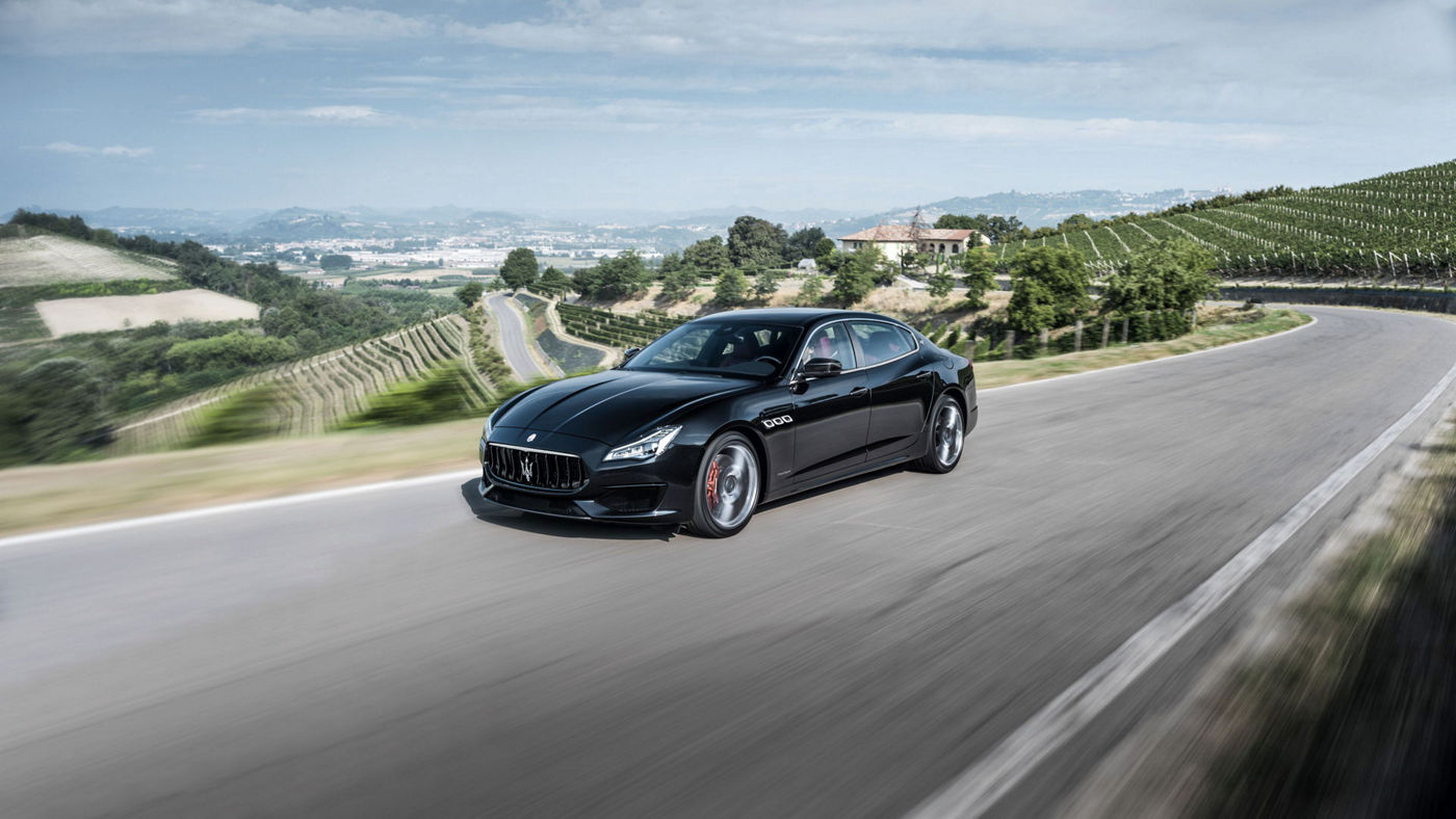 Front and side view of a black Maserati Quattroporte driving in countryside - all-wheel drive system