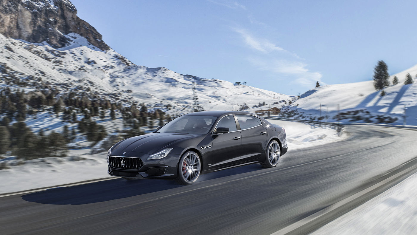 A black Maserati Quattroporte running on a snowy road