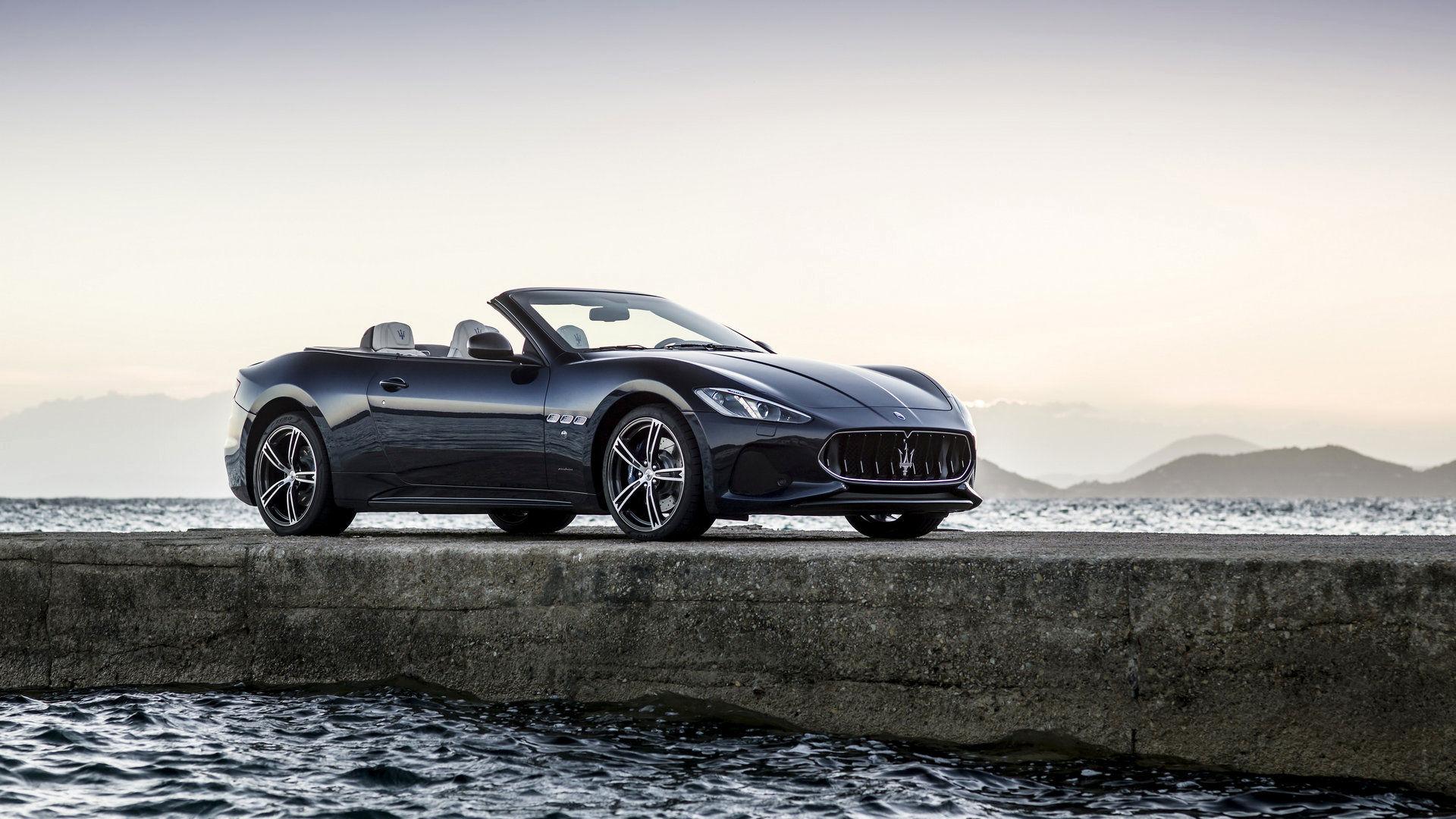 Maserati GranCabrio, decappottabile del Tridente, su un molo circondato dal mare durante un tramonto estivo