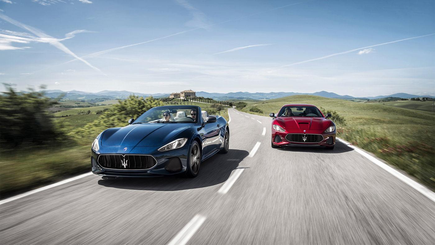 Roter und blauer Maserati GranTurismo und GranCabrio fahren durch eine schöne Landschaft