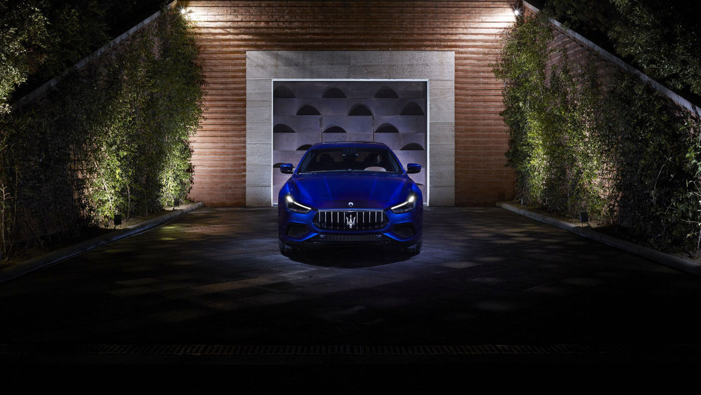Maserati Ghibli S Q4 with its headlights lit - front view - greenery wall on the background