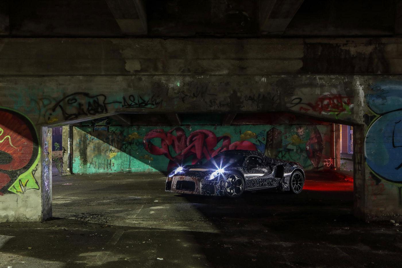 nuovo prototipo auto Maserati vista frontale con sfondo graffiti e fari accesi