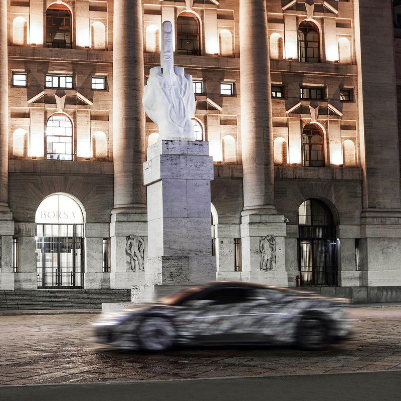 Prototipo del nuevo superdeportivo Maserati MC20 - Vista lateral del vehículo en movimiento a los pies de la escultura de Maurizio Cattelan L.O.V.E en Milán.
