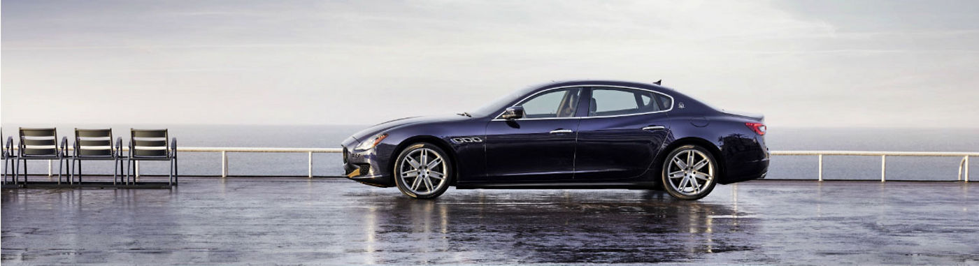 Blue Maserati Quattroporte - Sedan - Side view - On the road
