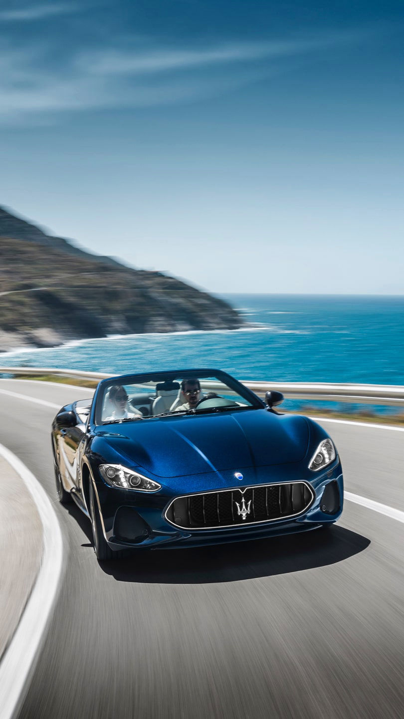 Maserati GranCabrio driving on a coastal road
