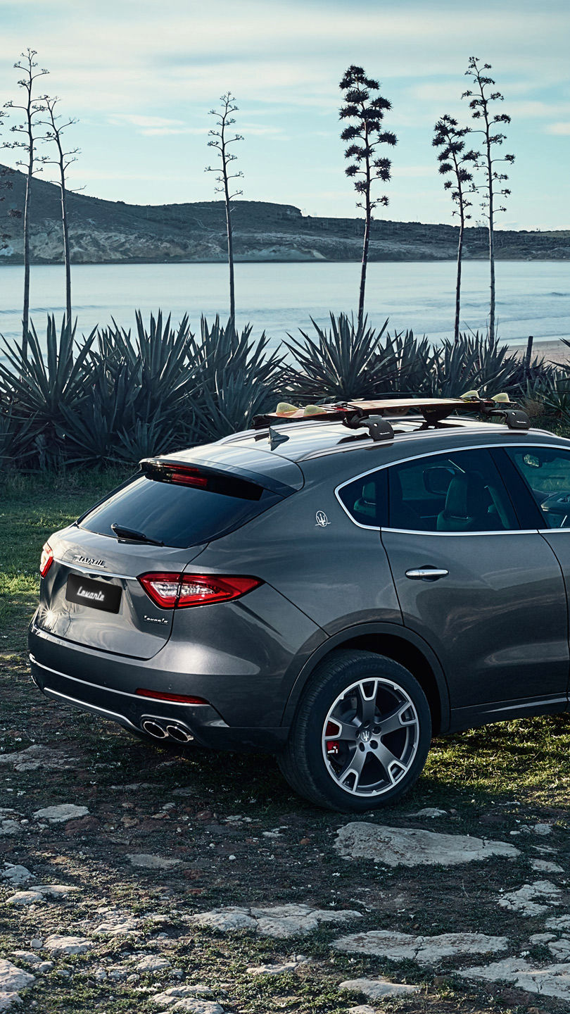 Maserati Levante, side view - on the road with a winter landscape background