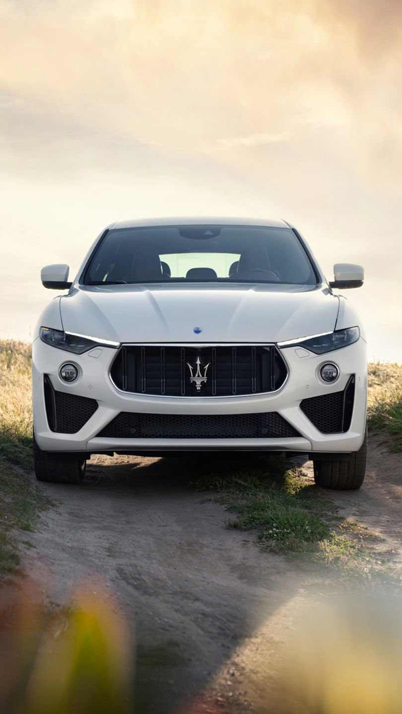 Maserati Levante on a gravel road - green field on the background