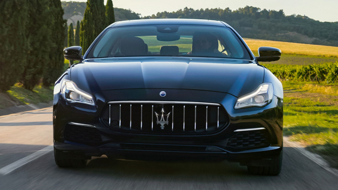 Maserati Quattroporte on the road, front view - green hills on the background