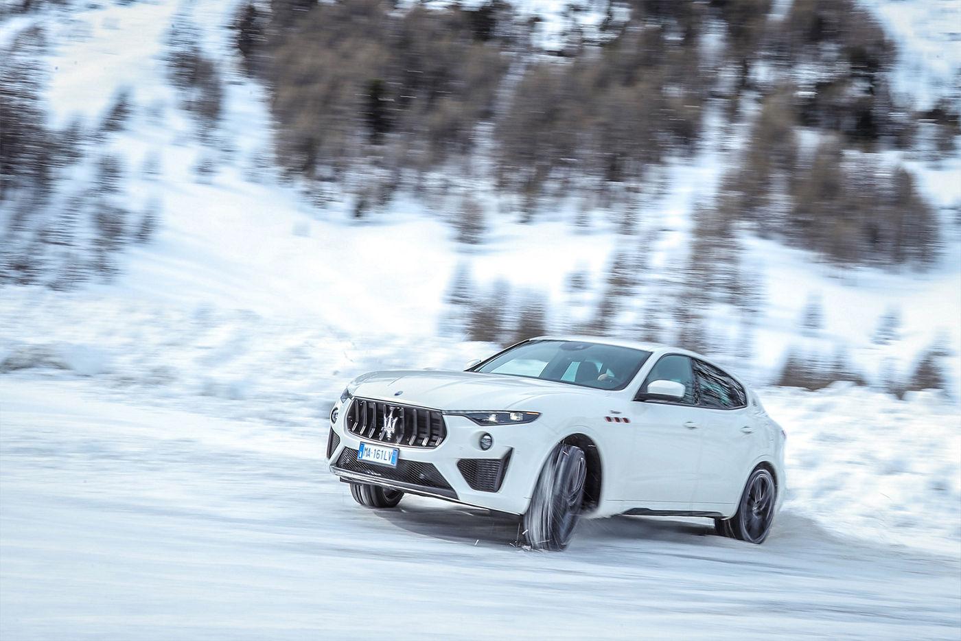 Maserati Levante fährt auf dem Schnee - Seitenansicht