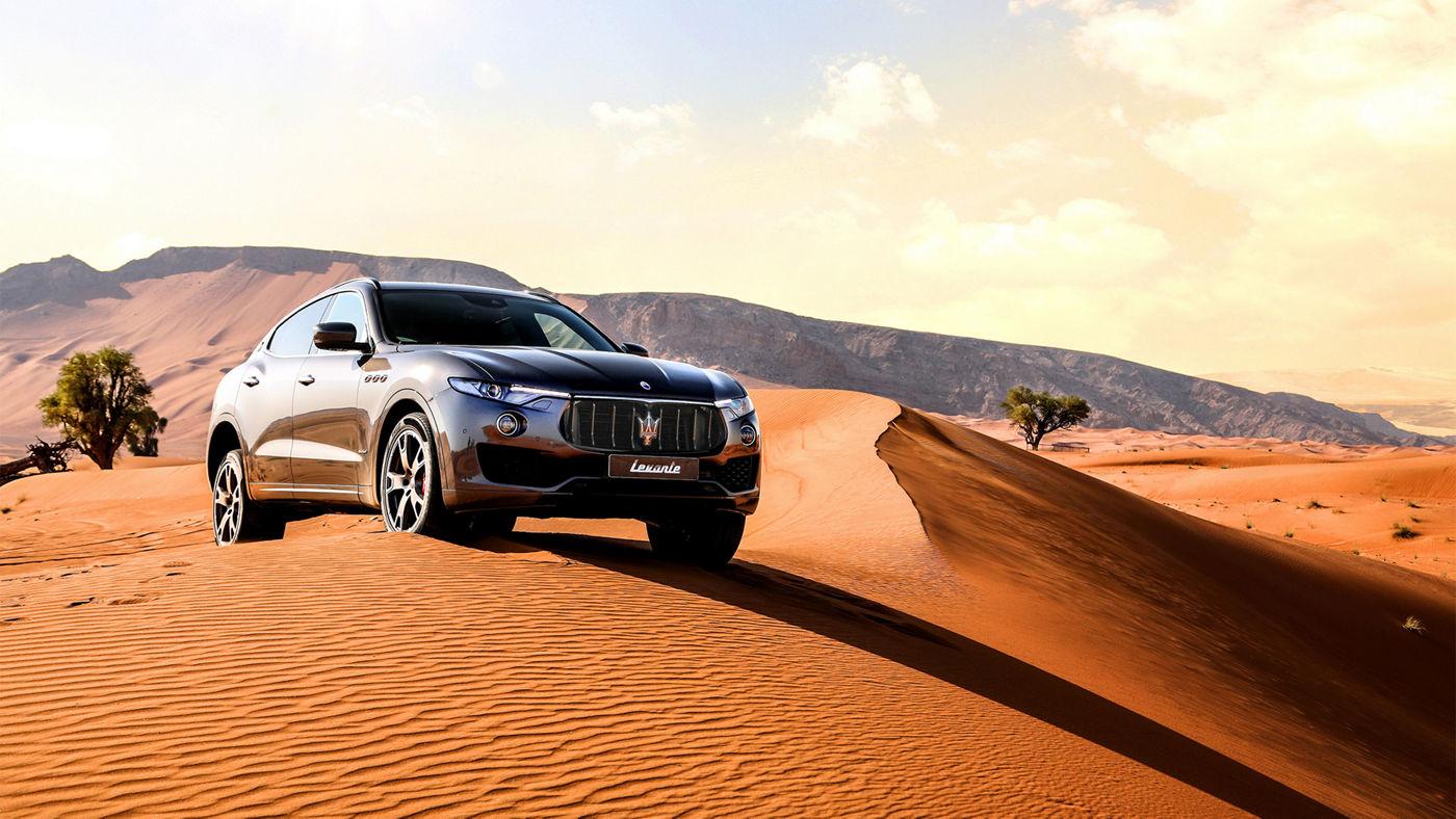 Maserati Levante gris au milieu du désert de Dubaï