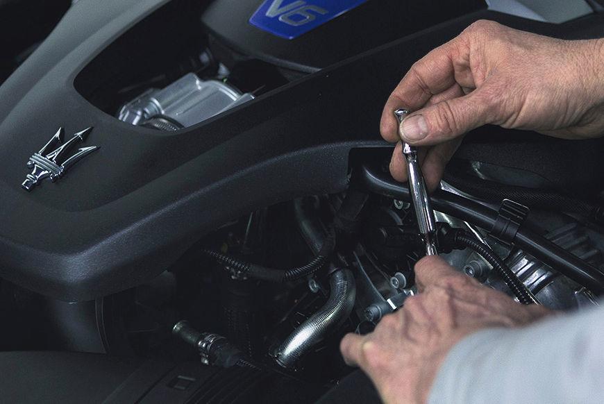 Zertifizierungsprozess der Maserati Gebrauchtwagen - Mann prüft Maserati Motor