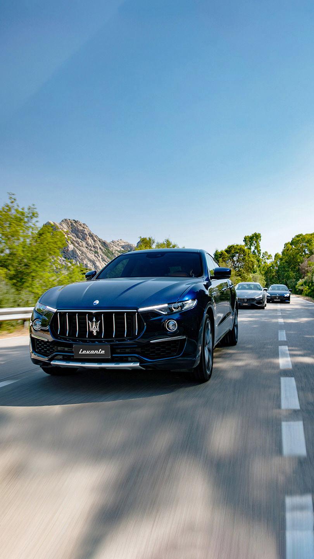 Blauer Maserati Levante fährt durch grüne Berglandschaft, zwei weitere Maseratis im Hintergrund