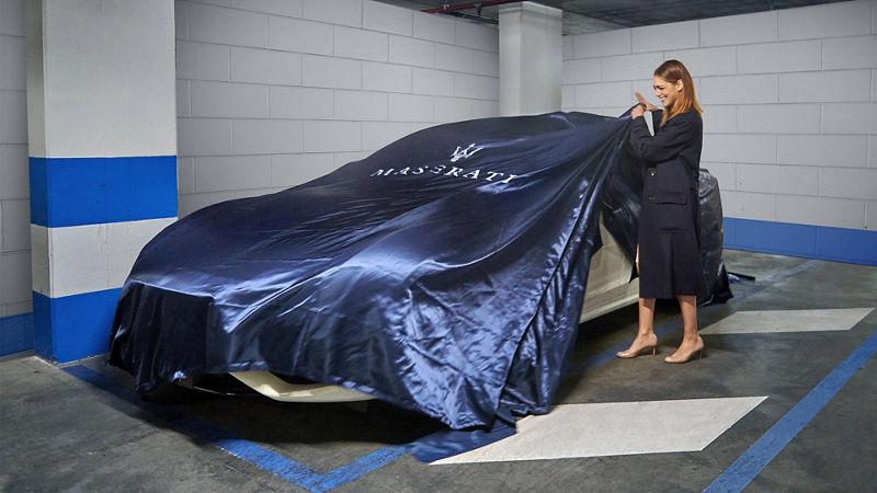 Miriam Leone deckt die Fahrzeugabdeckhaube des Maserati Ghibli Hybrid Gransport ab - Journey of Audacity