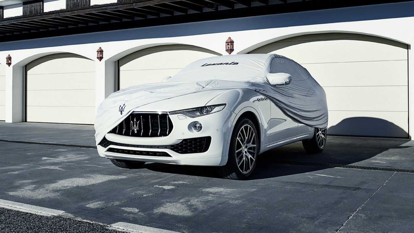 A Maserati-branded outdoor car cover draped on a white Maserati Levante.