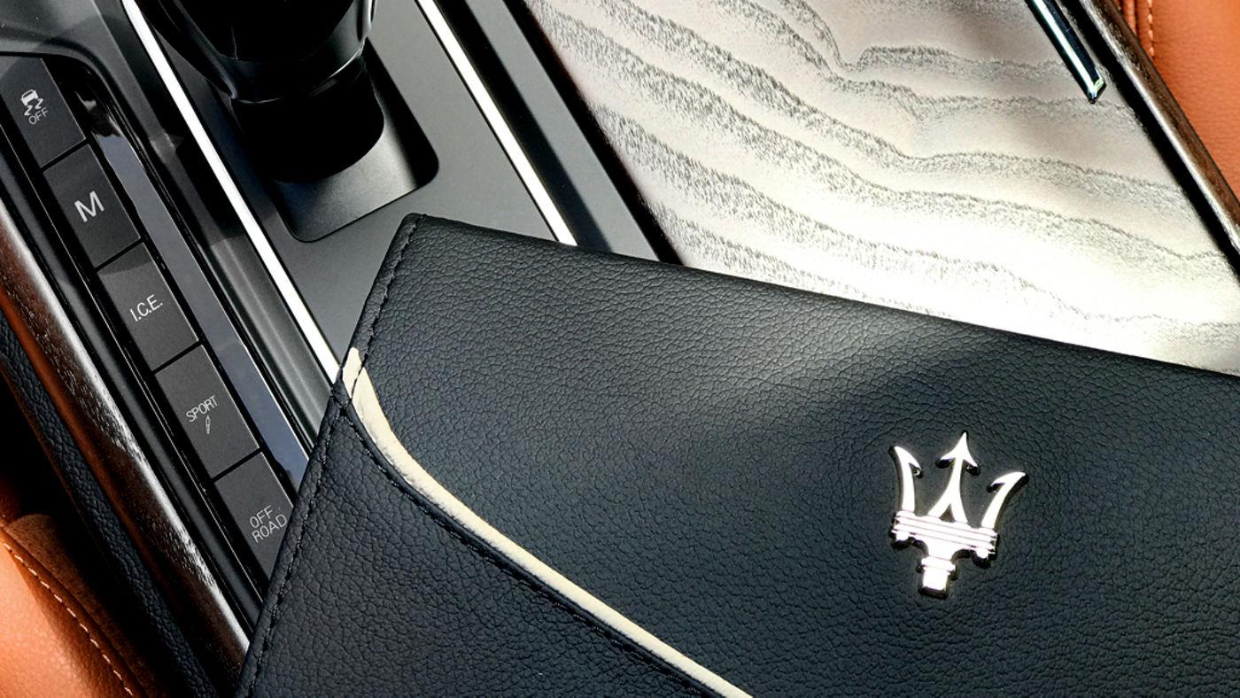 Un manuel du propriétaire placé sur la console centrale d'une Maserati Levante.