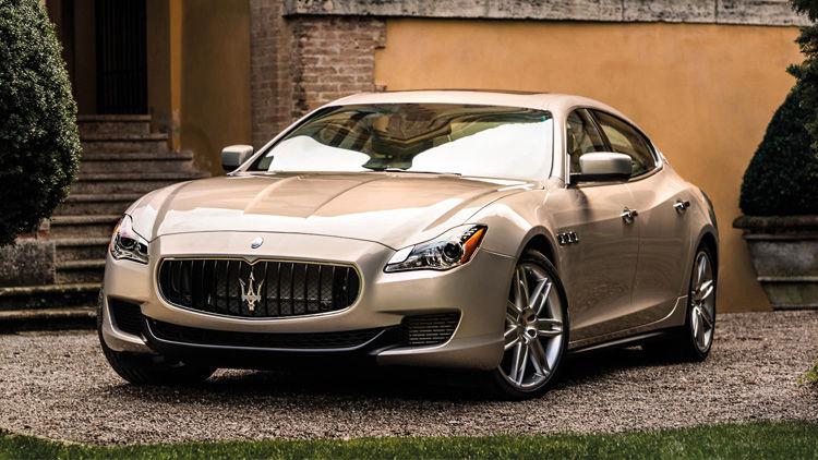 Une vue avant de trois quarts d'une Maserati Quattroporte devant une villa.