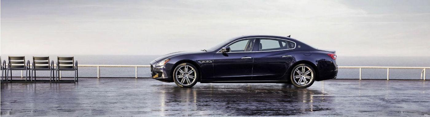 Une Maserati Quattroporte bleue de profil au bord de la mer.