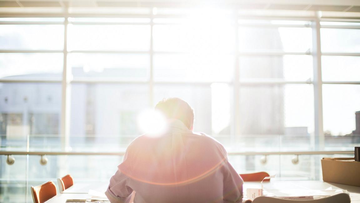 Man sat at desk in front of window with sun flare