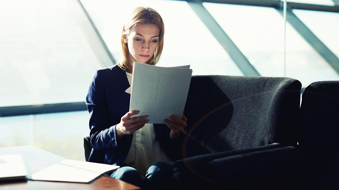 Young female professional reading paperwork in front of brightly lit windows