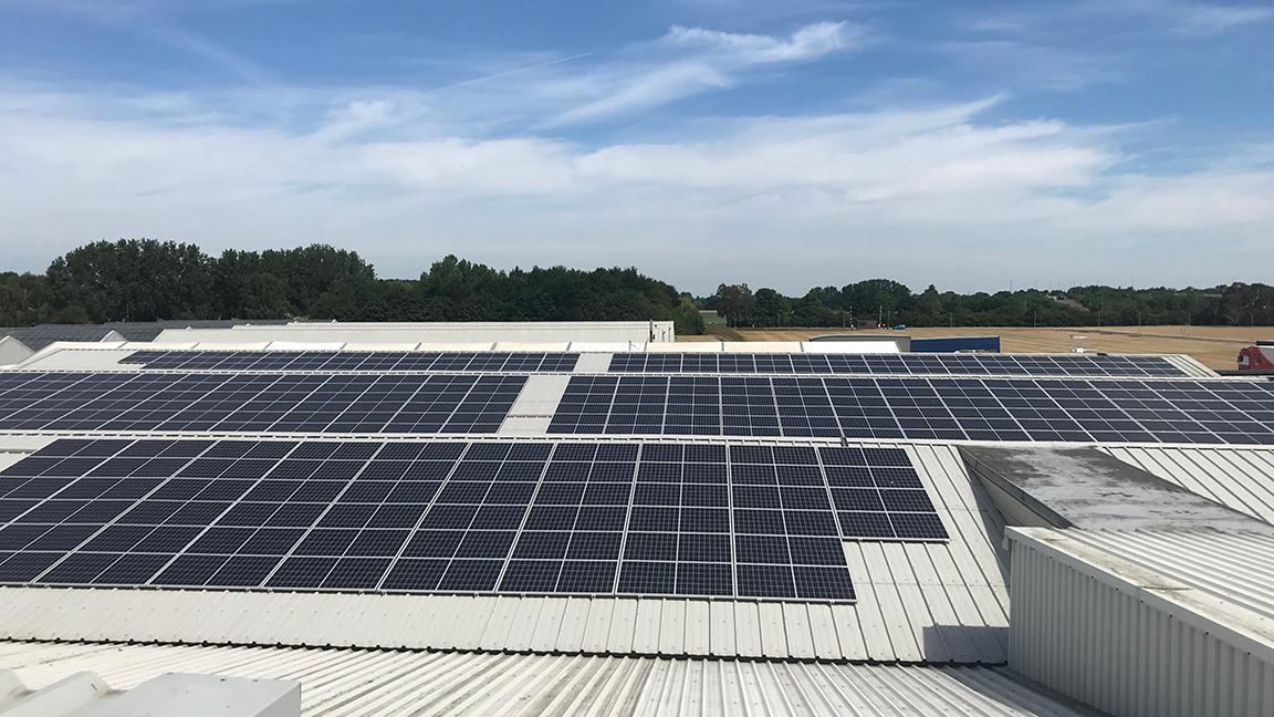 Solar panels on industrial building roof with blue sky above