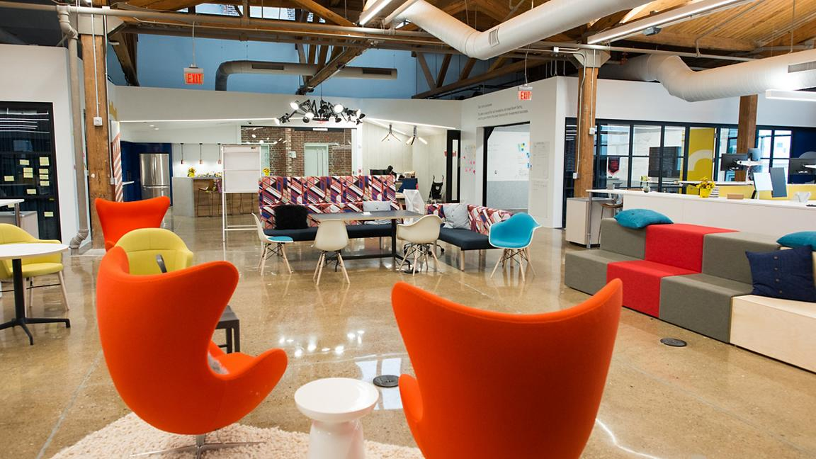 Modern open plan office interior with colourful chairs