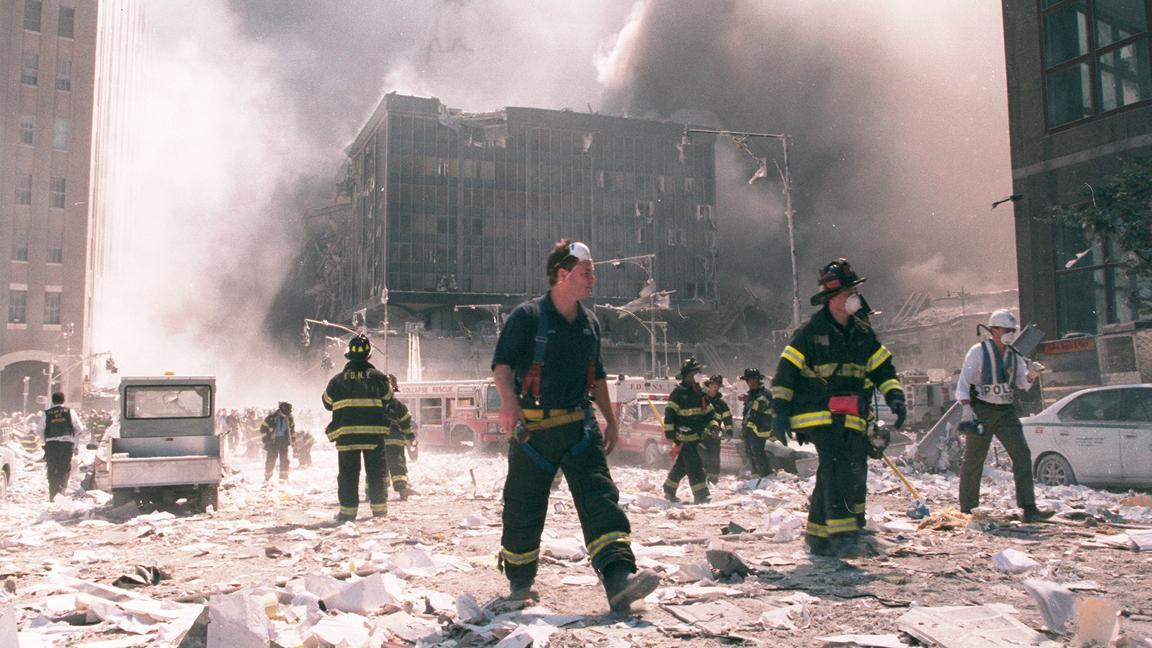 Firefighters walking in rubble from 9 11 attack