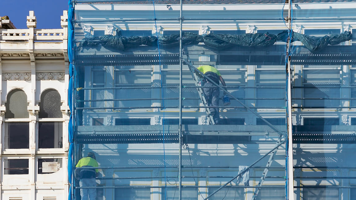 construction workers in scaffolding on the building facade for restore, repair and renovate