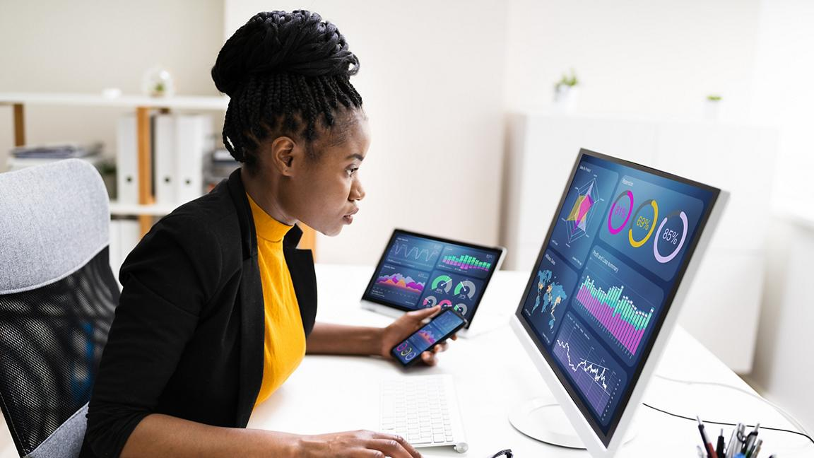 Black woman sits at desk analysing data on computer, tablet and phone