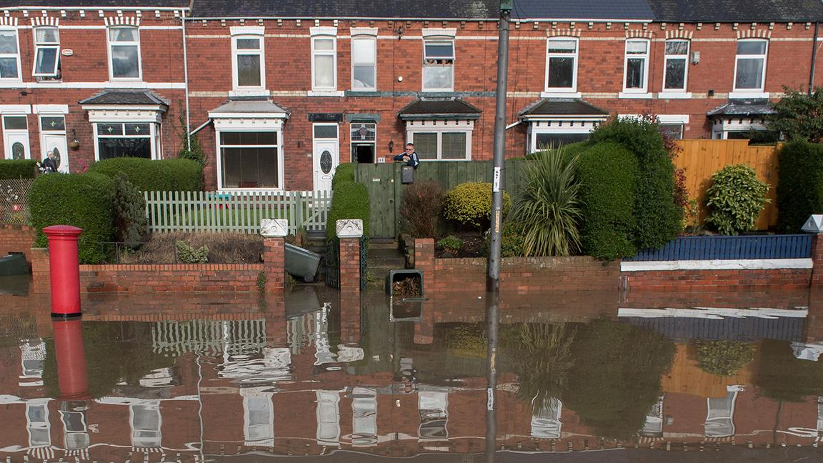 Terraced houses in Middlesbrough reflected in floodwater outside their properties