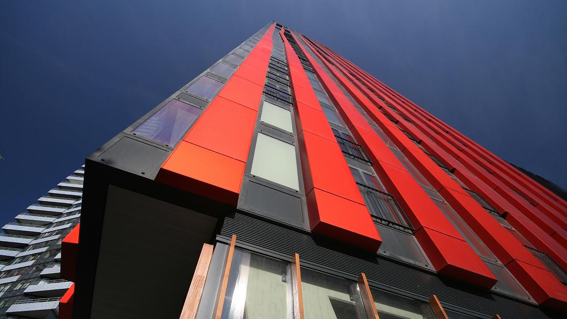 Tall building with vertical red panels, shot from low level looking up