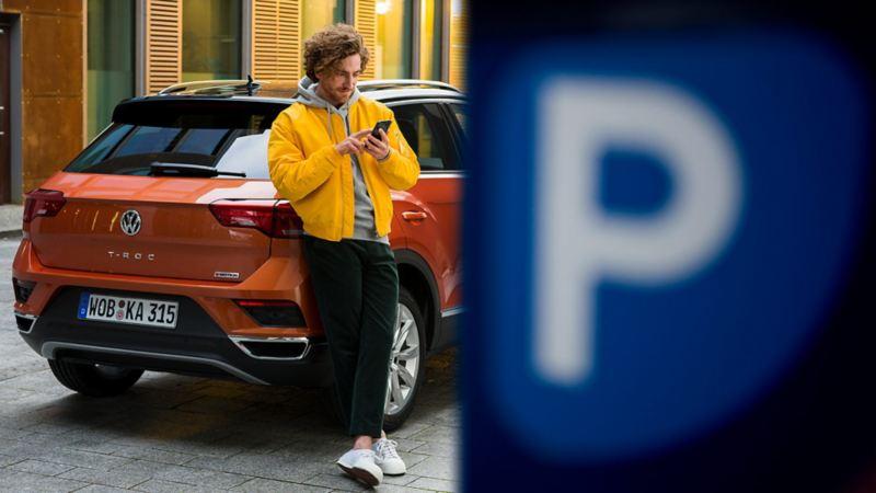 Mann mit Smartphone lehnt an Volkswagen T-Roc