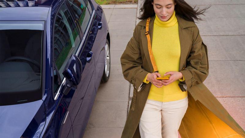 Frau vor ihrem parkenden Volkswagen
