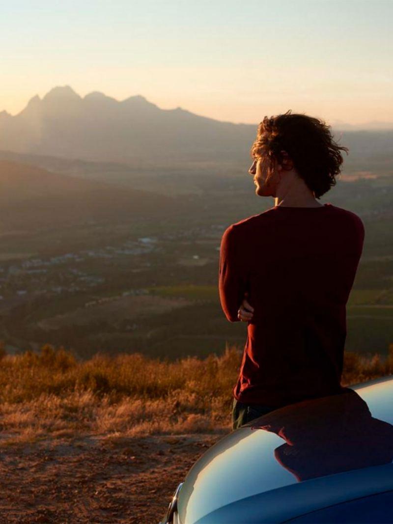 Ragazzo appoggiato sul cofano di una vettura Volkswagen ammira il panorama