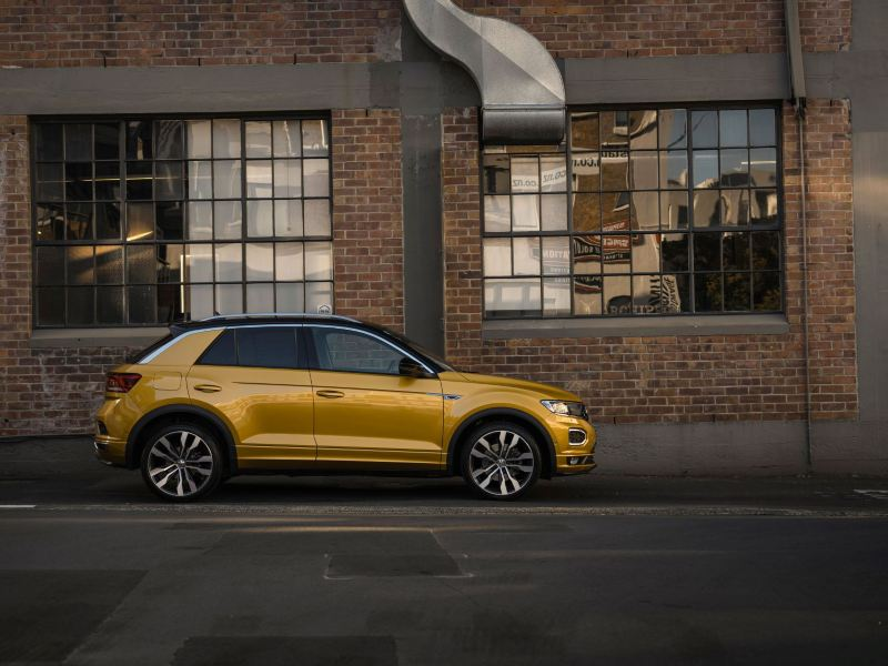 A yellow T-Roc driving on the streets at night
