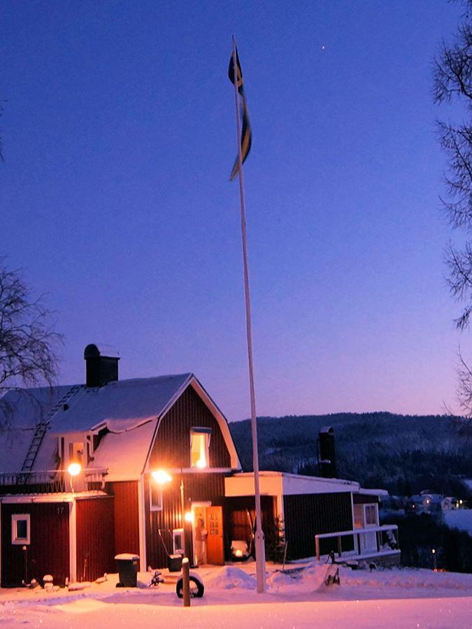 Ein einladend erleuchtetes Schwedenhaus steht in einer abendlichen Winterlandschaft.