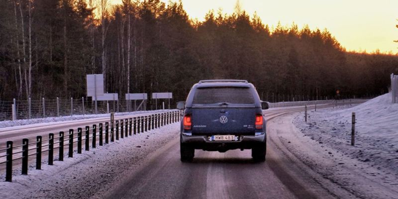 Ein Amarok von hinten. Er fährt eine verschneite Straße entlang.