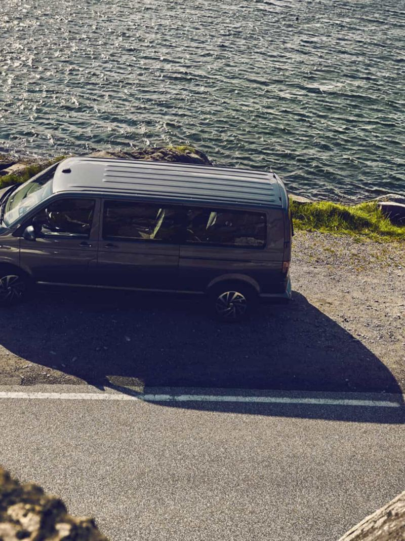 Un utilitaire Volkswagen Caravelle arrêté sur le bord d'une route, surmontant une falaise.