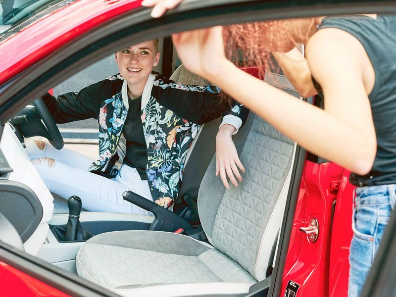 Two ladies one in the drivers seat, the other at the open passenger door of a red Volkswagen up!