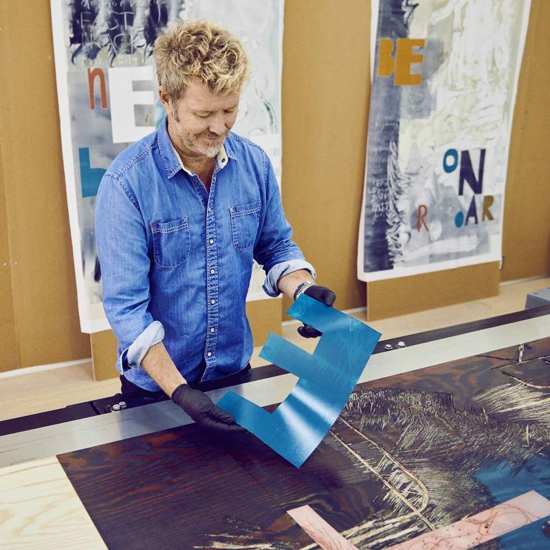 Magne Furuholmen en train de peindre des lettres dans son atelier.